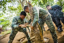 Philippine Marine Corps Cpl. Jason Tallud with Battalion Landing Team 4, 3rd Marine Brigade, instructs participants on how to make fire using bamboo during Jungle Survival training in Puerto Princesa, Philippines, during exercise Balikatan 2015, April 28. The Jungle Survival training, taught by the Philippine Marine Corps, was held to instruct military members as well as practice techniques to become more effective when responding to crisis in the region.