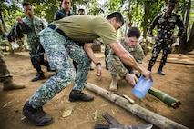Philippine Marine Corps Cpl. Jason Tallud with Battalion Landing Team 4, 3rd Marine Brigade, pours water into a bamboo pot during Jungle Survival training in Puerto Princesa, Philippines, during exercise Balikatan 2015, April 28. The Jungle Survival training, taught by the Philippine Marine Corps, was held to instruct military members and practice techniques to become more effective when responding to crisis in the region.