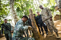 Philippine Marine Corps Cpl. Jason Tallud with Battalion Landing Team 4, 3rd Marine Brigade, shows U.S. Army Staff Sgt. Jerome Holland, a combat medic with Civil Affairs Team 742, Delta Company, 97th Civil Affairs Battalion, how to make fire using bamboo during Jungle Survival training in Puerto Princesa, Philippines, during exercise Balikatan 2015, April 28. The Jungle Survival training, taught by the Philippine Marine Corps, was held to instruct military members as well as practice techniques to become more effective when responding to crisis in the region.