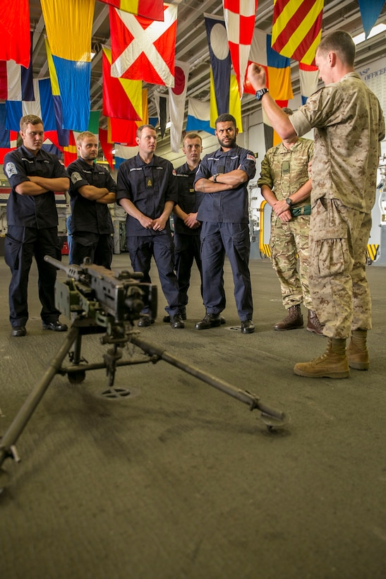 U.S. Marine Corps Lance Cpl. Charlie Wheeler, right, a motor transportation operator with the 22nd Marine Expeditionary Unit (MEU), gives a presentation on the M2 .50 caliber machine gun to British Royal Navy sailors with the HMS Lancaster during a tour aboard the amphibious assault ship USS Wasp (LHD 1) while out at sea April 30, 2015. Marines and U.S. Navy Sailors with the 22nd MEU from Marine Corps Base Camp Lejeune, N.C., participated in Navy Week 2015 in New Orleans April 23-29 and Fleet Week Port Everglades, Fla., May 4-10. The purpose of Navy Week was to showcase the strength and capabilities of the Navy-Marine Corps team through tours, static displays and community relations events, providing the public the opportunity to meet and interact with Marines and Sailors. (U.S. Marine Corps photo by Sgt. James R. Smith/Released)