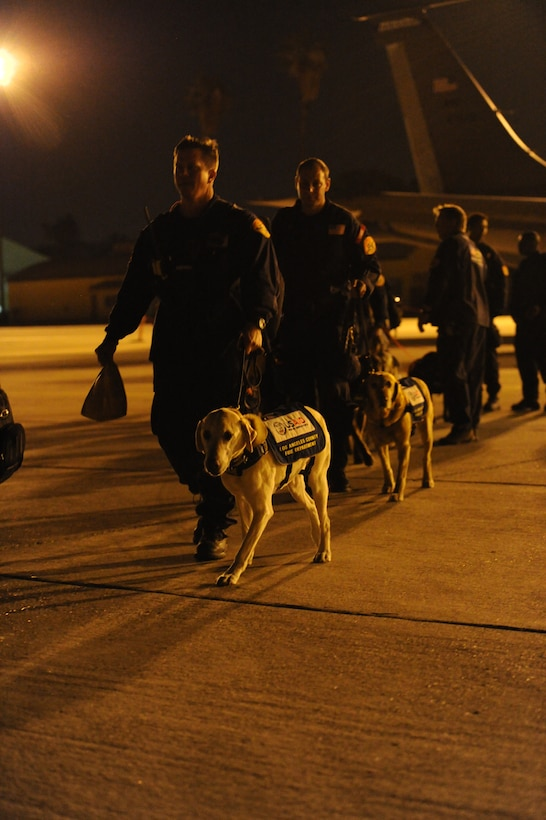 Canine handlers from an elite 57-person team, known as the Urban Search and Rescue Task Force 2 (CA-TF2), board a C-17 Globemaster III aircraft at March ARB, Calif., April 26, 2015. The CA-TF2 team, sponsored by the Los Angeles County Fire Department, Calif., was activated by the U.S. Agency for International Development's Office of U.S. Foreign Disaster Assistance on Sunday to deploy to Nepal in support of earthquake emergency rescue operations. (U.S. Air Force photo/Senior Airman Russell S. McMillan)