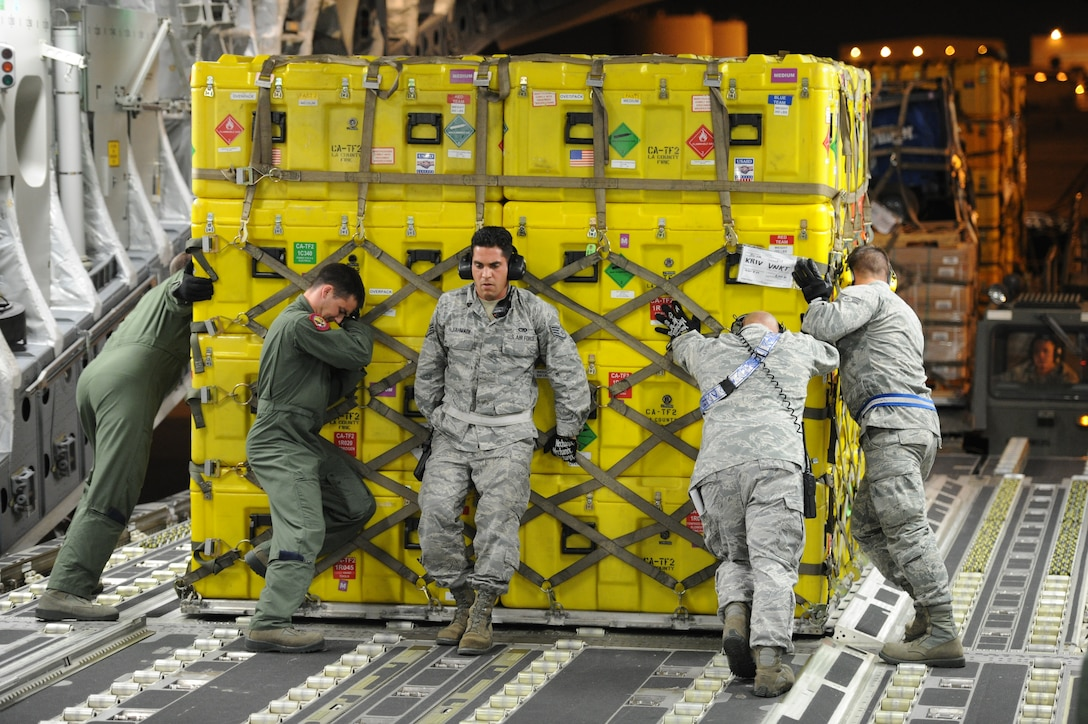 Airmen from March Air Reserve Base, Calif., and Joint Base Charleston, S.C., reposition a pallet of cargo on a C-17 Globemaster III aircraft at March ARB, Calif., April 26, 2015. The equipment includes sonar detection devices, heavy concrete cutting equipment, generators and more that will be used by an elite 57-person team, known as the Urban Search and Rescue Task Force 2 (CA-TF2), in support of earthquake emergency rescue operations in Nepal. (U.S. Air Force photo/Senior Airman Russell S. McMillan)