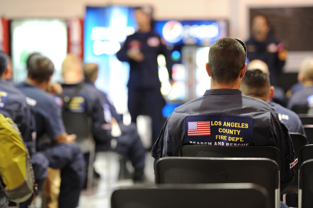 Members from Urban Search and Rescue Task Force 2 (CA-TF2), sponsored by the Los Angeles County Fire Department, Calif., attend a briefing regarding local customs the team should be aware of once reaching Nepal at the deployment hangar at March Air Reserve Base, Calif., April 26, 2015. The 57-person team was activated by the U.S. Agency for International Development's Office of U.S. Foreign Disaster Assistance in support of earthquake emergency rescue operations in Nepal. (U.S. Air Force photo/Senior Airman Russell S. McMillan)