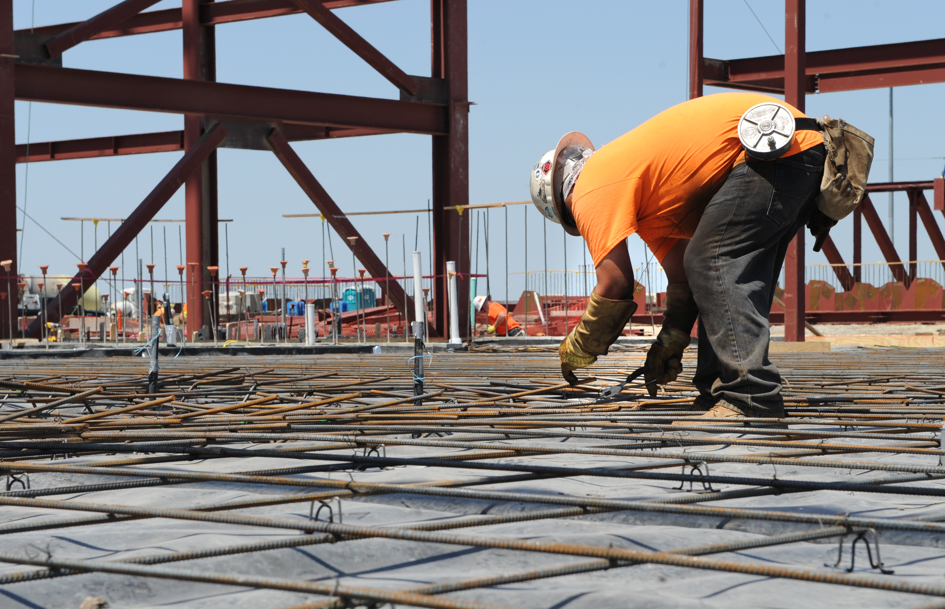 a construction worker secures a piece of rebar to the floor of hangar 1125 april