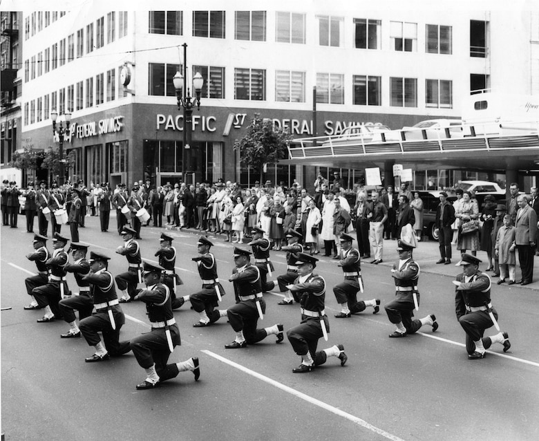 "A slightly larger formation of OreANG Precision Rifle Drill Team members perform their signature ""Queen Anne Salute"" in front of the reviewing stand during a parade in downtown Portland in the early 1960's.  (142FW History Archives)"