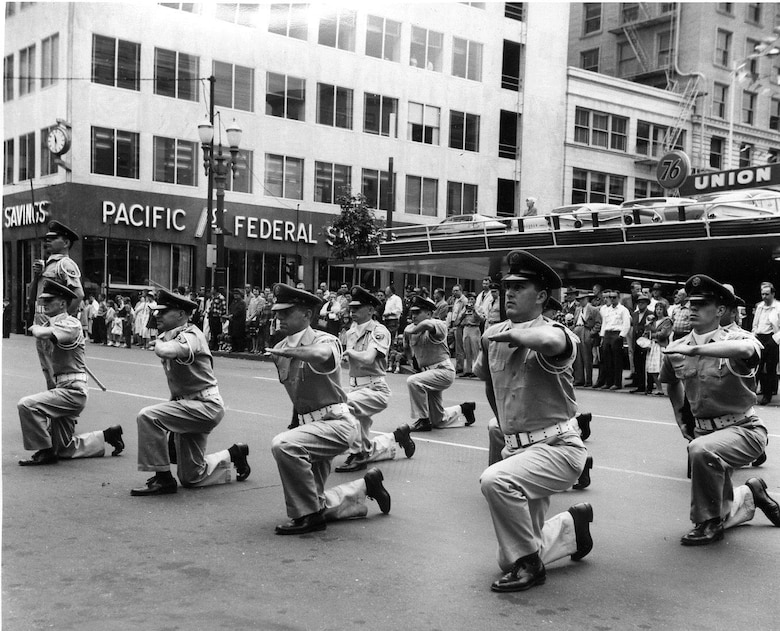 "OreANG Precision Rifle Drill Team members perform the ""Queen Anne Salute"" in front of the official reviewing stand during the May 20, 1961, Armed Forces Day Parade in downtown Portland, near the Pioneer Square post office.  Note the Team Leader with sword raised to left.  (142FW History Archives)"