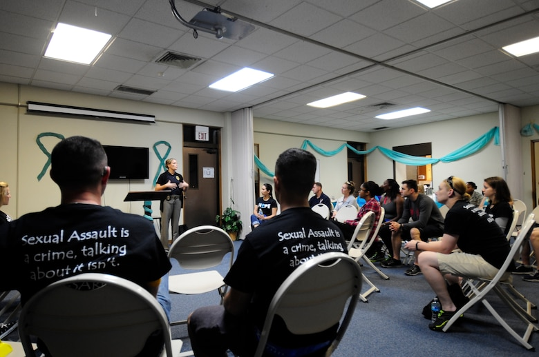 Desiree Santillan, U.S. Air Force Office of Special Investigations agent, spoke to the marchers about the importance of mandatory reporting inside Chapel 2 on Kadena Air Base, Japan, May 1, 2015.  She emphasized how leaders can make the difference in reporting even though it may be hard or cause them difficulty. (U.S. Air Force photo/Senior Airman Omari Bernard)