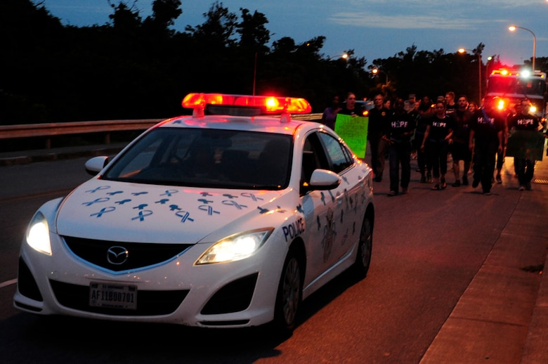 An 18th Wing Security Forces patrol car decorated in teal ribbons leads the Take Back the Night march on Kadena Air Base, Japan, May 1, 2015. The participants marched from the Schilling Community Center parking lot toward Chapel 2 with noise makers and cowbells, while chanting, symbolizing survivors reclaiming the night, the time when sexual assaults are most likely to occur. (U.S Air Force photo/Senior Airman Omari Bernard)