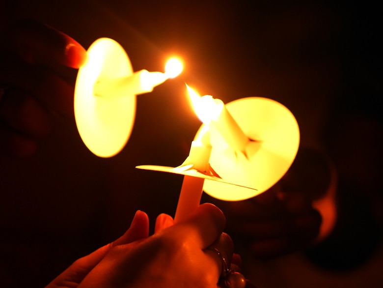 Victim advocates light candles during the Take Back the Night march on Kadena Air Base, Japan, May 1, 2015. Each individual lights the candles of those around them to illuminate the night and symbolize unity and togetherness. (U.S. Air Force photo/Senior Airman Omari Bernard)