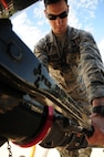 Airman 1st Class Jake McSheffrey, 509th Logistics Readiness Squadron fuels distribution technician, attaches a single point nozzle to an R-11 truck at Whiteman Air Force Base, Mo., April 23, 2015. The single point nozzle attaches to the bottom loader, to verify that the metered fill issued prior to filling. (U.S. Air Force photo by Senior Airman Keenan Berry/Released)