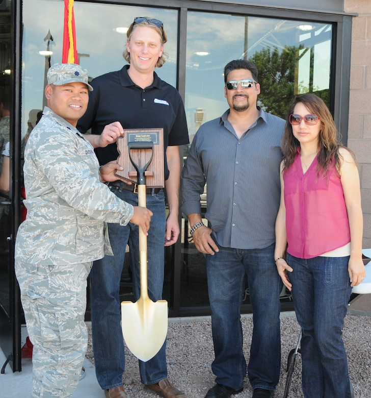 Lt. Col. Eric Queddeng, 161st Civil Engineer Squadron commander, presents a plaque to Brandon Carr, Jerome Padgett, and Gabby Zendejas of the contracted construction crew at the ribbon cutting ceremony for the wing's new stand-alone fitness center at the Phoenix Air National Guard base, May 2. At 2,400 square-feet, the first ever stand-alone fitness center to be built on an Air National Guard base after the base's original construction will accommodate nearly twice as many Airmen as the old facility. (U.S. Air National Guard photo by Tech. Sgt. Courtney Enos)