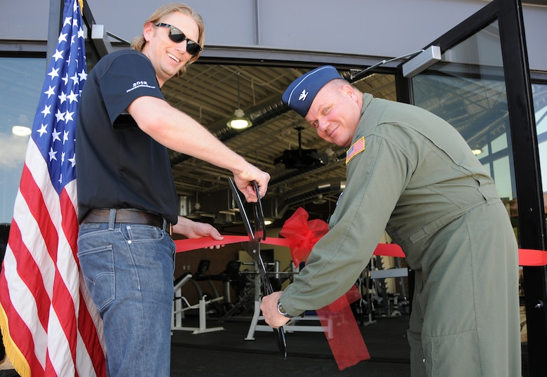 Col. Gary Brewer, 161st Air Refueling Wing commander, and Brandon Carr of the contracted construction crew, commemorate the wing's new fitness center at a ribbon cutting ceremony at the Phoenix Air National Guard base, May 2. At 2,400 square-feet, the first ever stand-alone fitness center to be built on an Air National Guard base after the base's original construction will accommodate nearly twice as many Airmen as the old facility. (U.S. Air National Guard photo by Tech. Sgt. Courtney Enos)