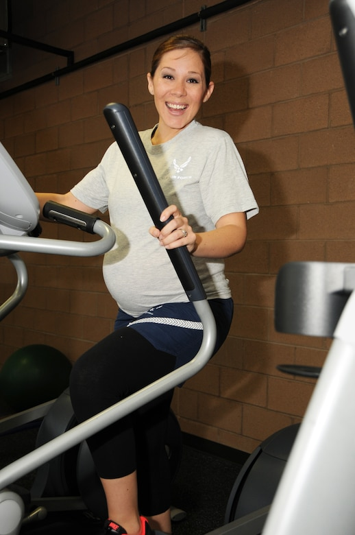 """Airman 1st Class Raquel Lewis, 161st Operations Group aviation resource manager, poses for a photo in the base fitness center at the Phoenix Air National Guard Base, May 3, 2015. Lewis is 31 weeks pregnant with her fourth son. """"It is important to me to be healthy and active during my pregnancy because I want to have a smooth labor and delivery, and be able to bounce back quickly for my other three kids,"""" said Lewis. (U.S. Air National Guard photo by Tech. Sgt. Courtney Enos)"""