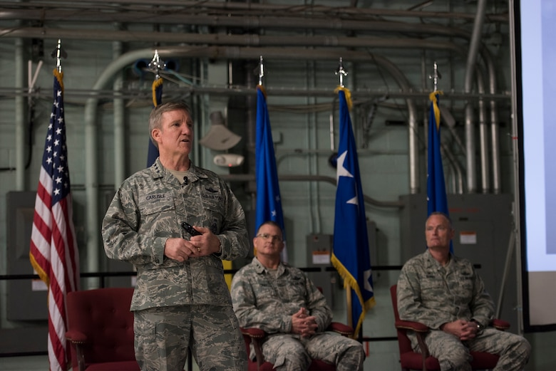 "U.S. Air Force Gen. Hebert J. ""Hawk"" Carlisle, commander of Air Combat Command, speaks to Airmen during an ""all call"" as Maj. Gen. Steven Cray, adjutant general, Vermont National Guard, and Col. Patrick Guinee, commander, 158th Fighter Wing, listen at Burlington International Airport, South Burlington, Vt., April 11, 2015. Visiting his first Air National Guard base as the COMACC, Carlisle met with leadership, had lunch with Airmen and recognized outstanding performers. (U.S. Air National Guard photo by Tech. Sgt. Sarah Mattison)"