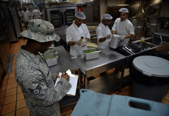 Staff Sgt. Demetrius, public health technician, takes notes during an inspection of the dining facility at an undisclosed location in Southwest Asia April 24, 2015. Here, the public health team is the lead agency responsible for assessing dining facility conditions and also checking to make sure food is properly stored and handled.  (U.S. Air Force photo/Tech. Sgt. Jeff Andrejcik)
