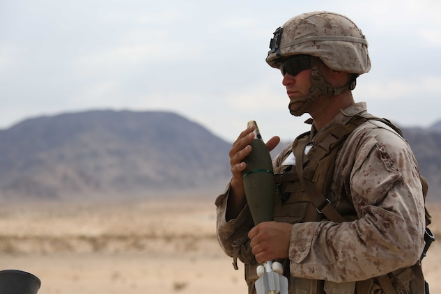 Sgt. Dustin Houghton, mortar man, Mortar Platoon, Weapons Company, Ground Combat Element Integrated Task Force, holds an 81mm mortar round during a Marine Corps Operational Test and Evaluation Activity assessment at Range 107, Marine Corps Air Ground Combat Center Twentynine Palms, California, April 24, 2015. From October 2014 to July 2015, the GCEITF will conduct individual and collective level skills training in designated ground combat arms occupational specialties in order to facilitate the standards-based assessment of the physical performance of Marines in a simulated operating environment performing specific ground combat arms tasks. (U.S. Marine Corps photo by Cpl. Paul S. Martinez/Released)