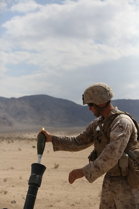 Sgt. Dustin Houghton, mortar man, with Mortar Platoon, Weapons Company, Ground Combat Element Integrated Task Force, loads an M252 81mm medium-weight mortar during a Marine Corps Operational Test and Evaluation Activity assessment at Range 107, Marine Corps Air Ground Combat Center Twentynine Palms, California, April 24, 2015. From October 2014 to July 2015, the GCEITF will conduct individual and collective level skills training in designated ground combat arms occupational specialties in order to facilitate the standards-based assessment of the physical performance of Marines in a simulated operating environment performing specific ground combat arms tasks. (U.S. Marine Corps photo by Cpl. Paul S. Martinez/Released)