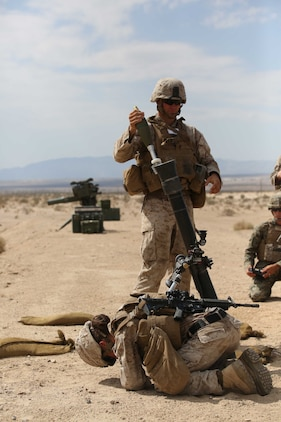 Sgt. Dustin Houghton, rear, and Cpl. Jacklyn Dean, front, both mortar men with Mortar Platoon, Weapons Company, Ground Combat Element Integrated Task Force, prepare to fire an M252 81mm medium-weight mortar during a Marine Corps Operational Test and Evaluation Activity assessment at Range 107, Marine Corps Air Ground Combat Center Twentynine Palms, California, April 24, 2015. From October 2014 to July 2015, the GCEITF will conduct individual and collective level skills training in designated ground combat arms occupational specialties in order to facilitate the standards-based assessment of the physical performance of Marines in a simulated operating environment performing specific ground combat arms tasks. (U.S. Marine Corps photo by Cpl. Paul S. Martinez/Released)