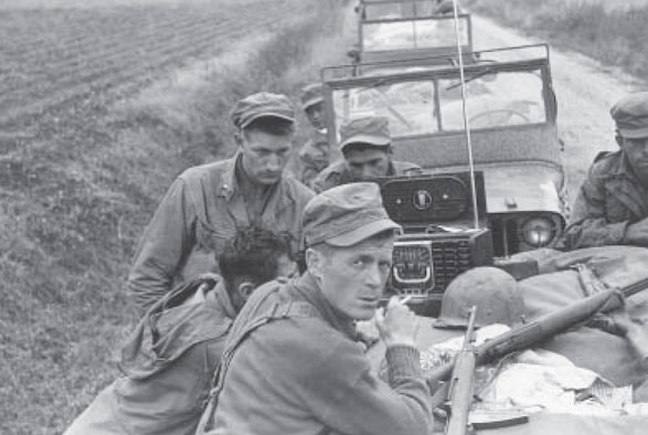 "Army Lt. Olin ""Short Round"" Hardy and L Company infantrymen wait to hear news on the radio during the Korean War.