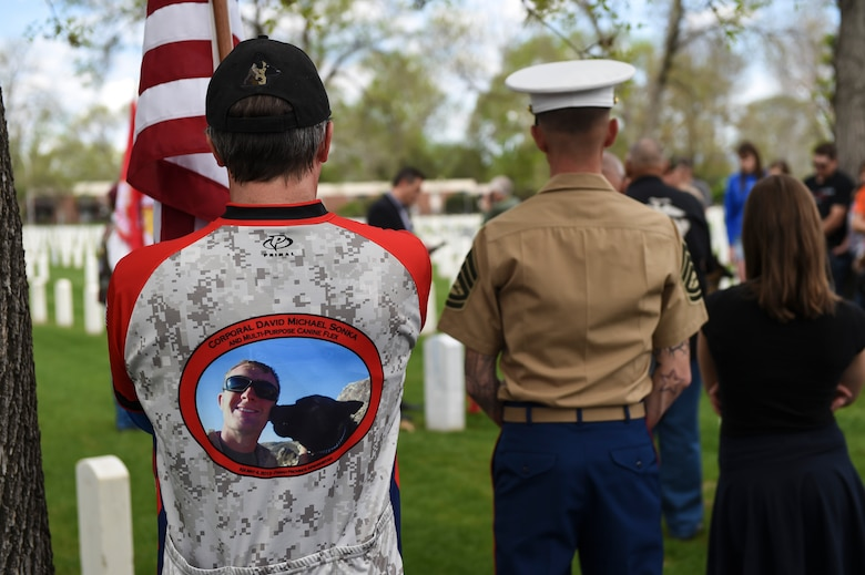 Family members and friends gather at the Cpl. David Sonka's Memorial Service May 2, 2015, at Fort Logan National Cemetery in Denver. The weekend's events were held to honor the life of Sonka, a U.S. Marine Corps Military Working Dog handler who was killed in action in Afghanistan May 4, 2013. The weekend's events included a motorcade to his grave, two memorial services, the reading of the names of all MWD and MWD handlers killed in action during Vietnam and recent years, a BBQ, and concluded with a multi-service dog handling competition. (U.S. Air Force photo by Senior Airman Phillip Houk/Released)