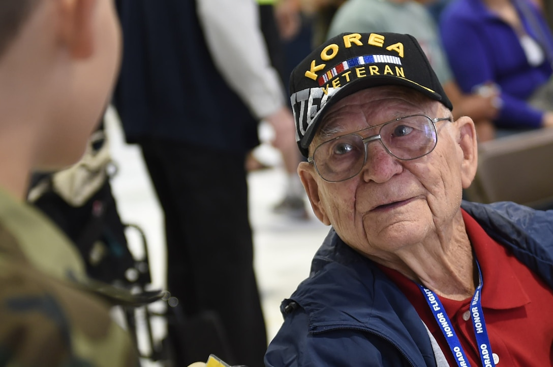 A Korea veteran speaks with two children before boarding a plane to May 3, 2015, at Denver International Airport in Denver. The veteran, along with 75 other World War II, Vietnam, Korea, terminally ill and Purple Heart recipient veterans, took a trip to Washington D.C. to visit military memorials. The overnight trip was hosted by the Honor Flight of Northern Colorado and is offered every year free of charge for the vets through donations from the public. (U.S. Air Force photo Airman 1st Class Samantha Meadors/Released)