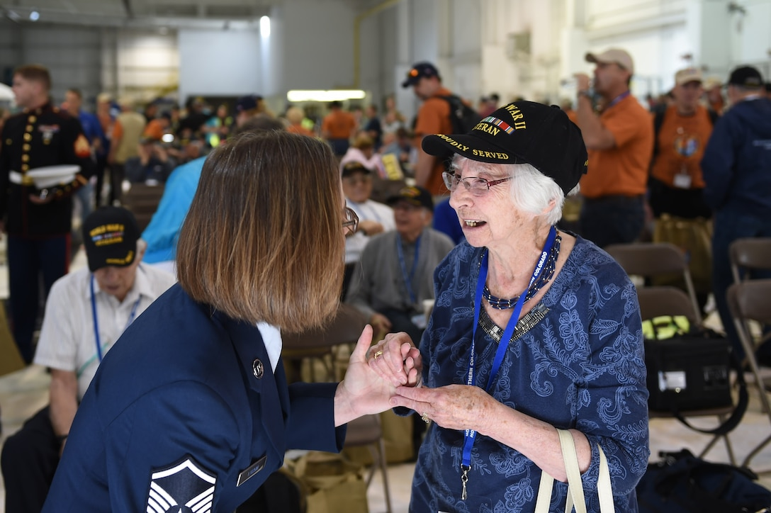 Master Sgt. Peggee Larkin, 566 Intelligence Squadron first sergeant, talks with a female World War II veteran before she boards a plane May 3, 2015, at Denver International Airport in Denver. The veteran, along with 75 other World War II, Vietnam, Korea, terminally ill and Purple Heart recipient veterans, took a trip to Washington D.C. to visit military memorials. The overnight trip was hosted by the Honor Flight of Northern Colorado and is offered every year free of charge for the vets through donations from the public. (U.S. Air Force photo Airman 1st Class Samantha Meadors/Released)