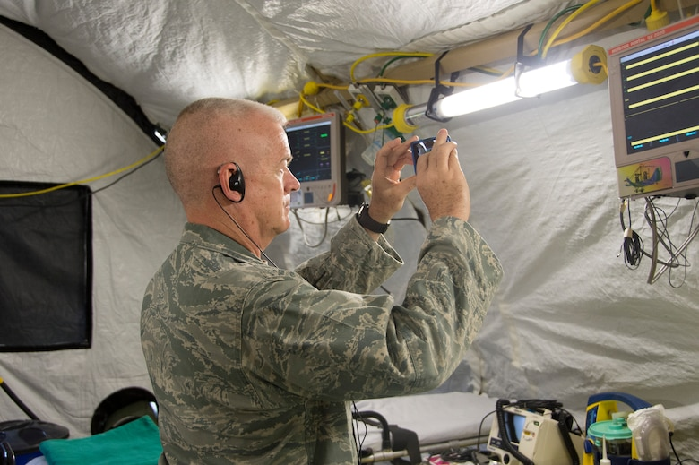 Col. Elmo Robison, Headquarters Air Force chief of expeditionary operations and policy, takes a photo of a portion of the EMEDS setup during an Expeditionary Medical Support training site visit on April 22, 2015, in Rio de Janeiro, Brazil. During the site visit members of AFSOUTH were able to get an up-close look at how their Brazilian counterparts setup the tents for EMEDS. (U.S. Air Force photo by Staff Sgt. Adam Grant/Released)