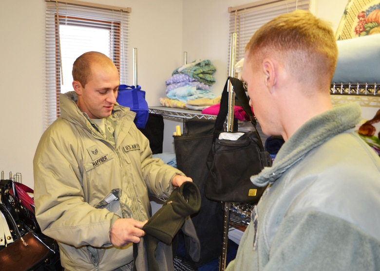 Aerospace Ground Equipment Mechanic Staff Sgt. Dustin Haffner shops for a coat that his son may be able to use at the new 120th Airlift Wing Airman's Attic on Dec. 6, 2014. The program provides an opportunity for members of the Montana Air National Guard to repurpose clean and serviceable clothing and household items. Air National Guard photo by Senior Master Sgt. Eric Peterson.
