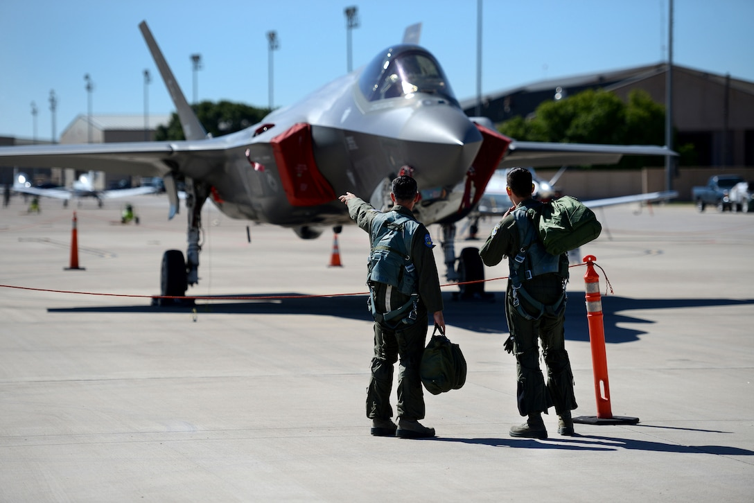 An instructor pilot with the 96th Flying Training Squadron, left, speaks with a student pilot about the F-35 Lightning II at Laughlin Air Force Base, Texas, May 1, 2015. As team XL seeks to graduate the world's best pilots, this experience provided the next-generation of warfighter's an opportunity to view the aircraft up-close and personal, receive briefings from the pilots and maintenance professionals and learn about its important role in the Air Force mission. (U.S. Air Force photo by Tech. Sgt. Steven R. Doty)