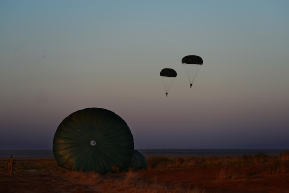Soldiers from the 193rd Infantry Brigade and Airmen from the 26th Special Tactics Squadron land after a parachute jump as a part of exercise Emerald Warrior April 28, 2015, at Melrose Air Force Range, N.M. Emerald Warrior is the Defense Department's only irregular warfare exercise, allowing joint and combined partners to train together and prepare for real-world contingency operations. (U.S. Air Force Photo/Airman 1st Class Shelby Kay-Fantozzi)