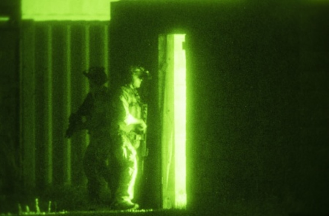 Navy SEAL team members prepare to breach a doorway during an Emerald Warrior close quarters combat exercise near Hurlburt Field, Fla., April 28, 2015. Emerald Warrior is the Defense Department's only irregular warfare exercise, allowing joint and combined partners to train together and prepare for real-world contingency operations. (U.S. Air Force photo/Senior Airman Cory D. Payne)