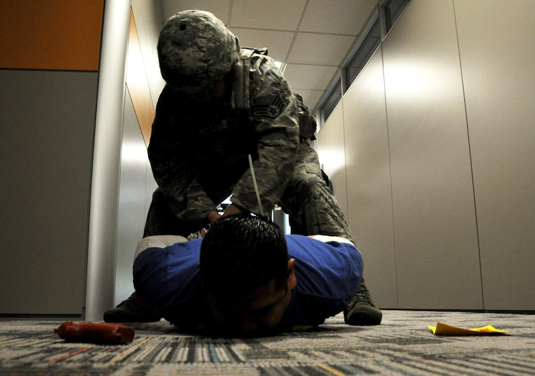 Staff Sgt. Adam Pollow, 94th Security Forces Squadron member, takes down Tech. Sgt. Michael Sapanza, 94th SFS member who was portraying the active shooter, during a training exercise in the 94th Aeromedical Staging Squadron April 23, 2015, at Dobbins Air Reserve Base, Ga. The 94th SFS provides active shooter training throughout the year and for individual units and organizations on the base to be better prepared for a real-world incident. (U.S. Air Force photo/Senior Airman Daniel Phelps)