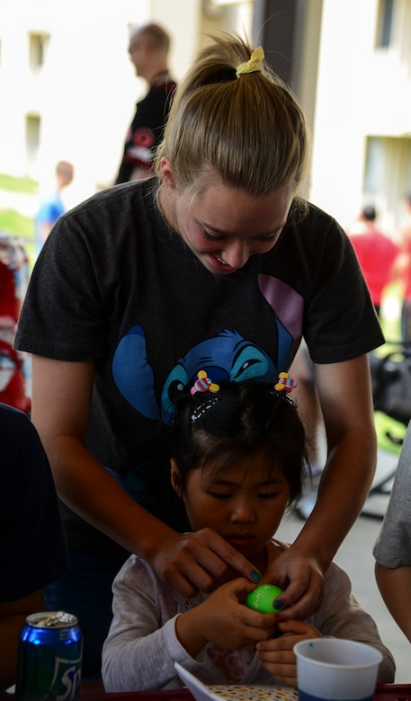 Avery Lokowich, daughter of Lt. Col. Luke Lokowich, 5th  Reconnaissance Squadron commander and a U-2 pilot, helps a young Korean girl from Lira Orphanage put stickers onto a colored egg during a 5th RS sponsored barbecue April 26, 2015, at Osan Air Base, Republic of Korea. The 5th RS visits the orphanage twice a year as well as invite them the base for barbecues. (U.S. Air Force photo by Senior Airman Matthew Lancaster)