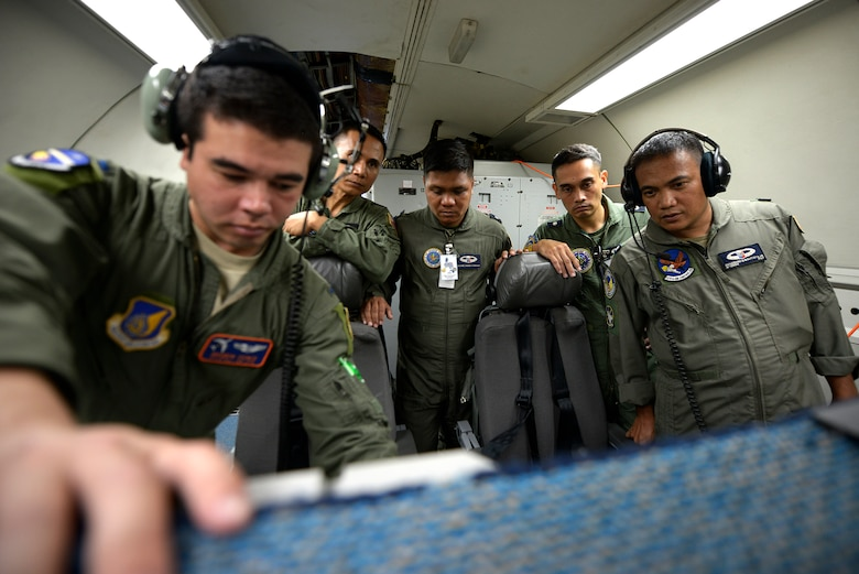 U.S. Air Force 1st Lt. Andrew Stokes, 961st Airborne Air Control Squadron (AACS) air weapons officer, demonstrates weapons systems operations with Philippines Air Force weapons controllers while onboard a 961st AACS E-3 Sentry Airborne Warning and Control System aircraft during Exercise Balikatan 2015 over the Philippines, April 23. This exercise marks the first time in history that PAF air battle managers have controlled other aircraft while onboard the AWACS. Since the exercise began, April 20, the 961st AACS has integrated 20 PAF weapons controllers during their missions to provide them with first-hand experience using the aircraft's systems. The 961st AACS is stationed at Kadena Air Base, Japan. (U.S. Air Force photo by Staff Sgt. Maeson L. Elleman)