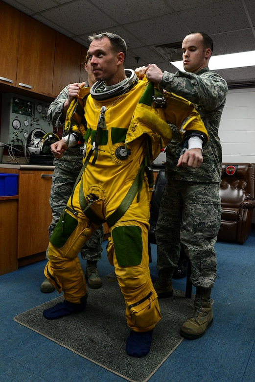 Staff Sgt. Stacy Klein and Staff Sgt. Joseph Kennedy, 5th Reconnaissance Squadron physiological technicians, assisit Lt. Col. Luke Lokowich, 5th RS commander and a U-2 pilot, with his high-altitude pressure suit April 22, 2015, at Osan Air Base, Republic of Korea. A pressure suit is a protective suit worn by pilots who may fly at altitudes where the air pressure is too low for an unprotected person to survive. (U.S. Air Force photo by Senior Airman Matthew Lancaster)