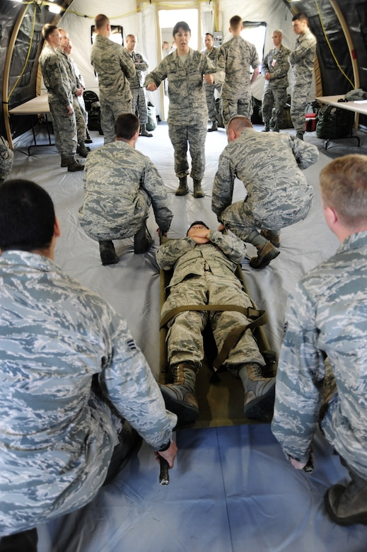 Oregon Air National Guard Tech. Sgt. Dena Johnson, assigned to the 142nd Fighter Wing, center, gives instructions on the proper way to lift and carry a simulated victim during medical training in the AEF Skills Rodeo, Aril 12, 2015. Portland Air National Guard Base, Ore. (U.S. Air National Guard photo by Tech. Sgt. John Hughel, 142nd Fighter Wing Public Affairs/Release)