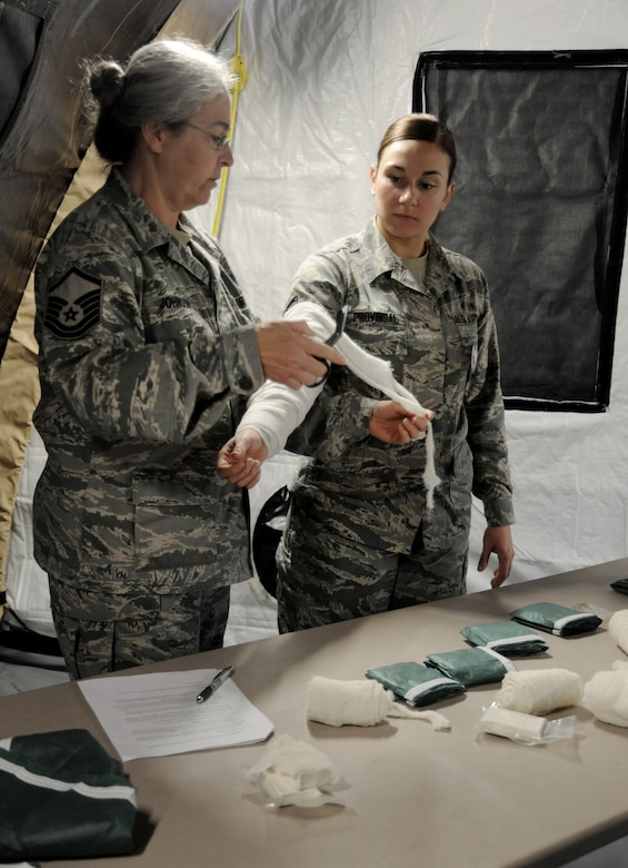 Oregon Air National Guard medic from the 116th Air Control Squadron, Master Sgt. Johnson , left demonstrates how to apply medical bandages to Airman 1st Class Kaitlyn Provincial , right during the AEF Skills Rodeo, April 12, 2015, Portland Air National Guard Base, Ore. (U.S. Air National Guard photo by Tech. Sgt. John Hughel, 142nd Fighter Wing Public Affairs/Release)