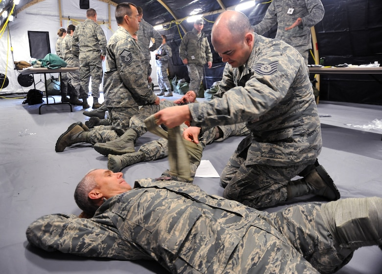 Oregon National Guard Tech. Sgt. George Sanders, right, applies a bandage to Maj. Paul Granada, left, during the AEF Skill Rodeo, April 12, 2015, Portland Air National Guard Base, Ore. Both Sanders and Granada are assigned to 142nd Fighter Wing Maintenance Group and are preparing for deployment with others members of the 142nd Fighter Wing. (U.S. Air National Guard photo by Tech. Sgt. John Hughel, 142nd Fighter Wing Public Affairs/Release)