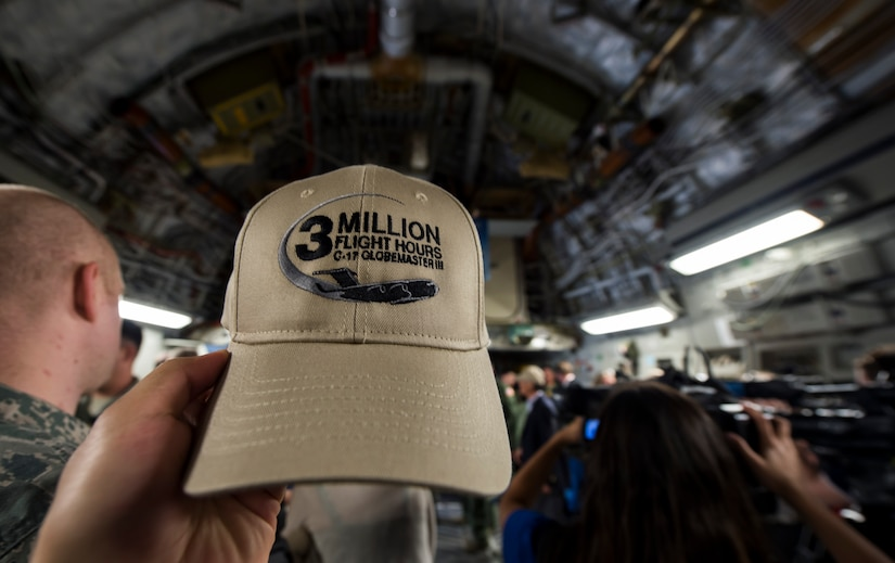 An Airman holds up a hat aboard a C-17 Globemaster III May 5, 2015 at Joint Base Charleston, S.C, during an event celebrating the C-17 surpassing the three millionth flying hour.  An aircrew from JB Charleston flew the plane here from Robins Air Force Base, Ga. The first C-17 flight was Sept. 15, 1991 and the Air Force currently has 222 C-17's in the fleet. (U.S. Air Force photo/Senior Airman Jared Trimarchi)