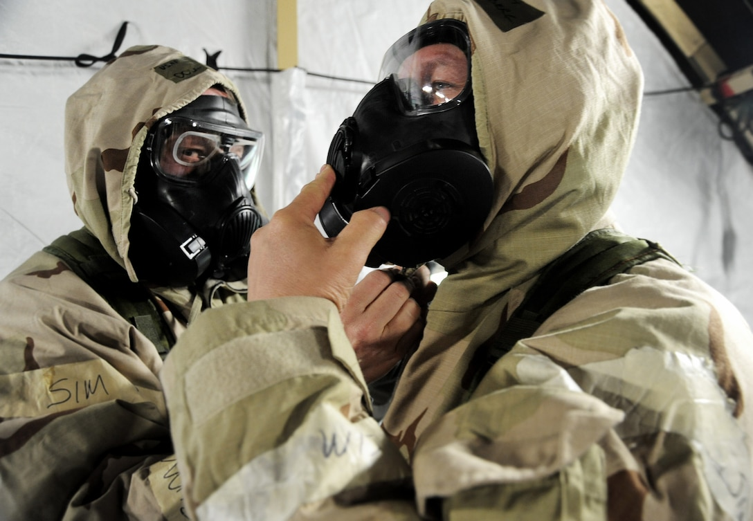 Oregon Air National Guard Airmen help each other with protective equipment during the AEF Skills Rodeo, April 12, 2015, Portland Air National Guard Base, Ore. (U.S. Air National Guard photo by Tech. Sgt. John Hughel, 142nd Fighter Wing Public Affairs/Release)