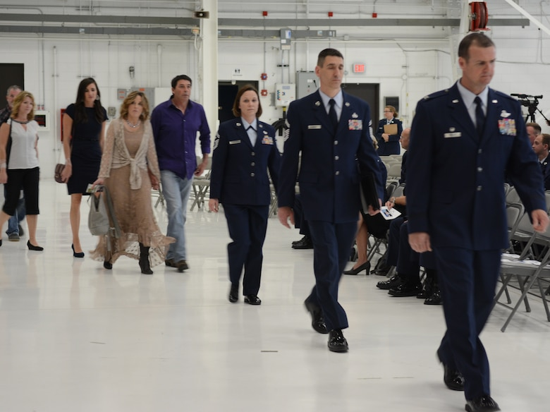 Col. Jeffrey J. Wiegand, 115th Fighter Wing commander, leads Airman 1st Class Kelly C. Tomfohrde's family to their seats prior the memorial service, May 3. Airmen of the 115 FW, family members and friends gathered to honor Tomfohrde's service, sacrifices and to recognize her achievements and dedication during the memorial service on base. (U.S. Air National Guard photo by Tech. Sgt. Tiffany Black)