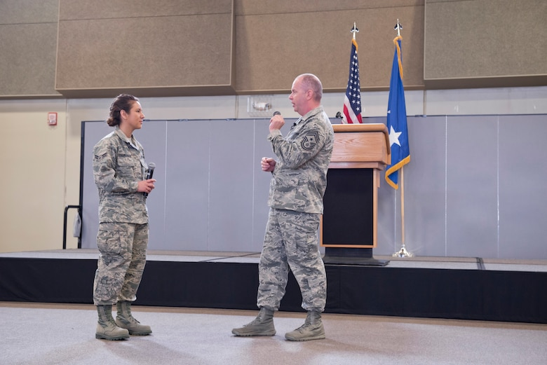 The Command Chief Master Sgt. of the Air National Guard (CCM ANG), Chief Master Sgt. James W. Hotaling (right) presents Airman 1st Class Jessica Thomerson (left), 132d Geospatial Intelligence, with his coin during the 132d Wing, Des Moines, Iowa May Off-Site Resiliency Event held at the Valley Community Center, West Des Moines, Iowa on Saturday, May 2, 2015; Thomerson is receiving Hotaling's coin because she shared her stories of Basic Military Training at Lackland Air Force Base, San Antonio, Texas with the group (per Hotaling's request).  The Director of the Air National Guard (DANG), Lt. Gen. Stanley E. Clarke III, is also in attendance, which marks the first time in history that both the DANG and CCM ANG visit an ANG wing together.  (U.S. Air National Guard photo by Tech. Sgt. Linda K. Burger/Released)