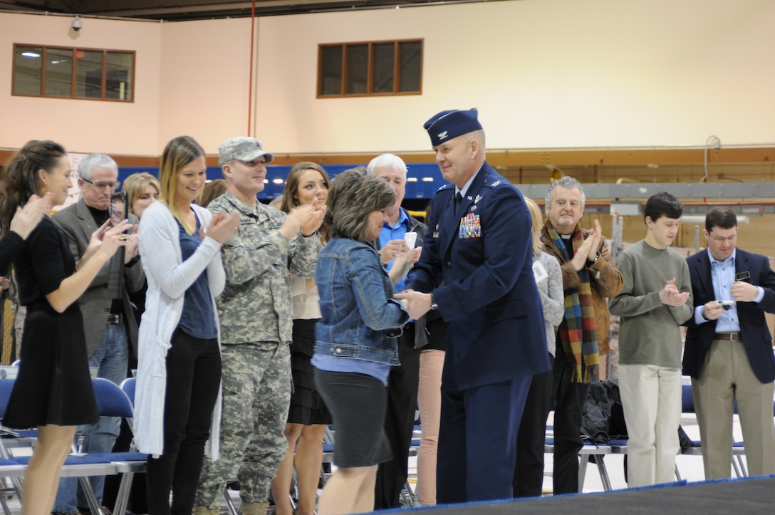 Col. Pete Hronek presents his first commander's coin to his wife, Tracy, for her years of support of the 120th Airlift Wing's Airmen during the unit's change of command ceremony March 7, 2015 in Great Falls. (Montana Air National Guard photo/Tech. Sgt. Michael Touchette)
