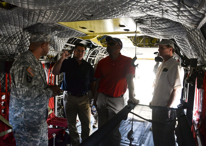 SOTO CANO AIR BASE, Honduras – A 1-228 Aviation Battalion crew chief explains the capabilities of the CH-47 Chinook to U.S. Ambassador to Honduras James Nealon (right),  Congressman Marc Veasey (center right), representing Texas' 33rd District, and Congressman Austin Scott (center left), representing Georgia's 8th District, during a congressional delegation visit May 4, 2015, at Soto Cano Air Base, Honduras. A versatile airframe, the CH-47 Chinook provides a broad range of support to U.S. and partner nation efforts to stabilize the Central American region. (U.S. Air Force photo by Staff Sgt. Jessica Condit)
