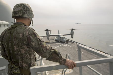 Republic of Korea Marine Corps Lt. Col. Jeong Hyung-Goo watches a U.S. Marine Corps MV-22B Osprey land on the flight deck of the Republic of Korea ship Dokdo (LPH 6111), at sea, March 26, 2015. This was the first time an Osprey has landed on a ROK amphibious assault ship. The aircraft is with Marine Medium Tiltrotor Squadron 262 (Reinforced), 31st Marine Expeditionary Unit. The Marines of the 31st MEU are embarked aboard the forward-deployed amphibious assault ship USS Bonhomme Richard (LHD 6) and are currently participating in Korean Marine Exchange Program 15 during the MEU's annual Spring Patrol of the Asia-Pacific region. (U.S. Marine Corps photo by SSgt. Joseph DiGirolamo/Released)
