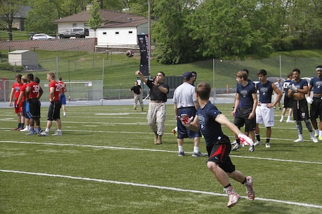Sergeant Matthew Garcia, a Marine Corps Recruiting Station Kansas City recruiter, throws a football downfield to receivers as part of a route-running drill during the Semper Fidelis All-American Football Camp at Rockhurst High School's Vincent P. Dasta Memorial Stadium May 3, 2015.