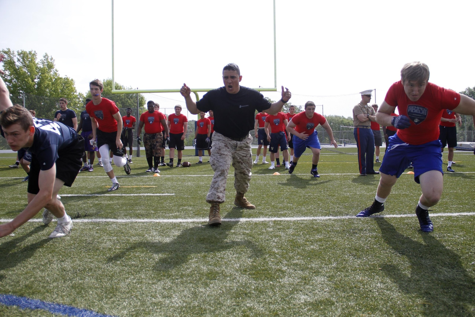 Sergeant Jose Marrufo, a Marine Corps Recruiting Station Kansas City recruiter, motivates football players to push through a sprint drill during the Semper Fidelis All-American Football Camp at Rockhurst High School's Vincent P. Dasta Memorial Stadium May 3, 2015. Approximately 195 players from across Missouri, Kansas, Arkansas, Nebraska, Illinois and Missippi took part in the all-day camp. NFL coaches were on hand to provide critical football skills and guidance to the camp attendees.