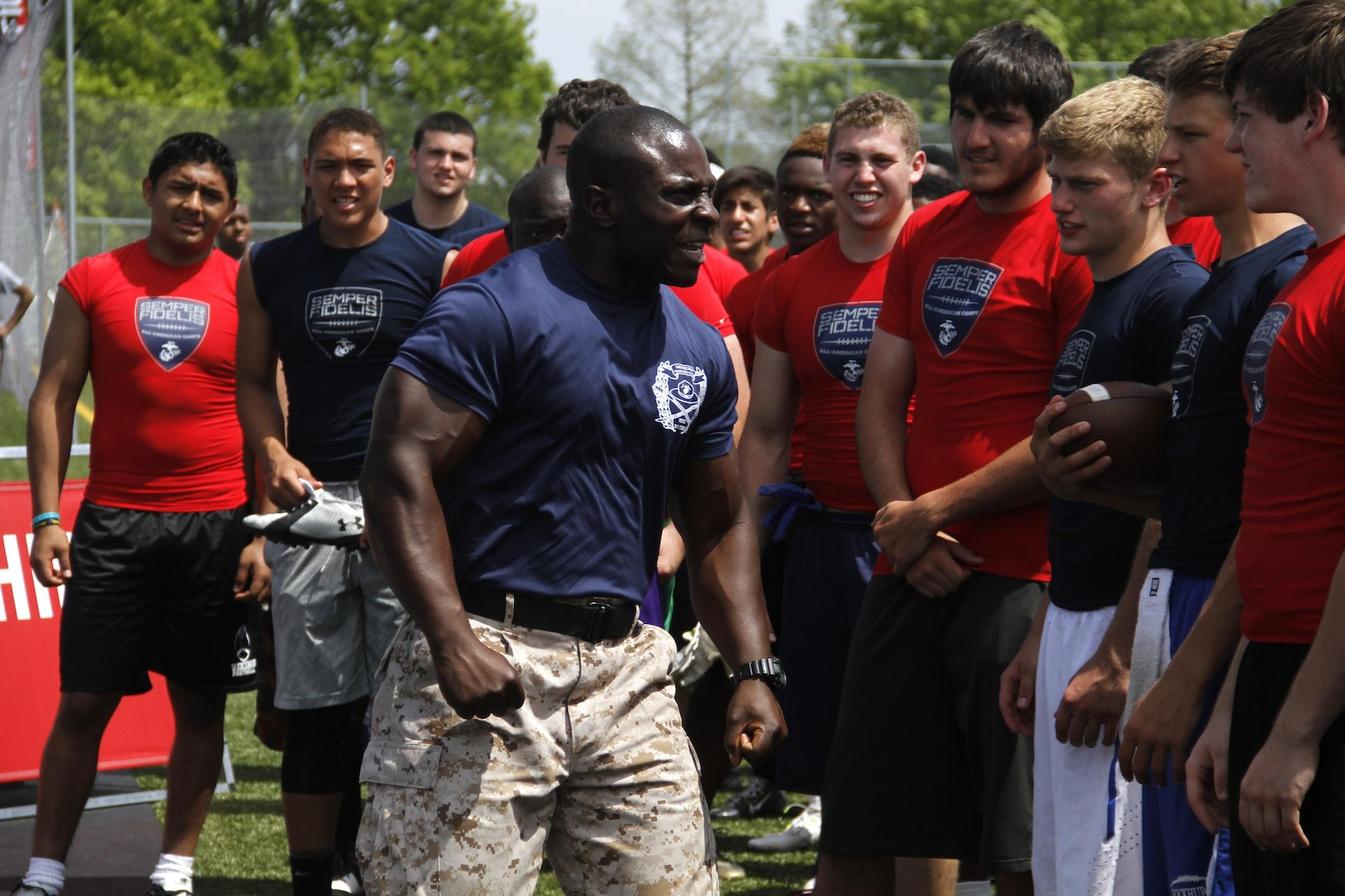 Gunnery Sergeant Aubrey L. McDade, Jr., a Company I, 3rd Battalion, Recruit Training Regiment, Marine Corps Recruit Depot San Diego chief drill instructor, motivates football players during the Semper Fidelis All-American Football Camp at Rockhurst High School's Vincent P. Dasta Memorial Football Stadium May 3, 2015.