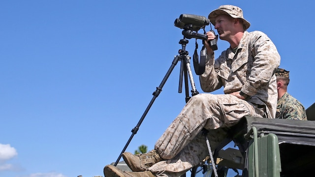 Sergeant Charles Holloway, the chief scout with Scout Sniper Platoon, Weapons Company, 2nd Battalion, 2nd Marine Regiment looks through his high-powered optics to locate a scout sniper candidate during a stalking exercise in the vicinity of SR-10 aboard Marine Corps Base Camp Lejeune, North Carolina, April 22, 2015. The stalking exercise taught Marines the importance of going undetected during movement and while firing at a target. The stalking exercise was one of many conducted by Marines attending the Scout Sniper Basic Preparation Course over the course of two weeks during the month of April.