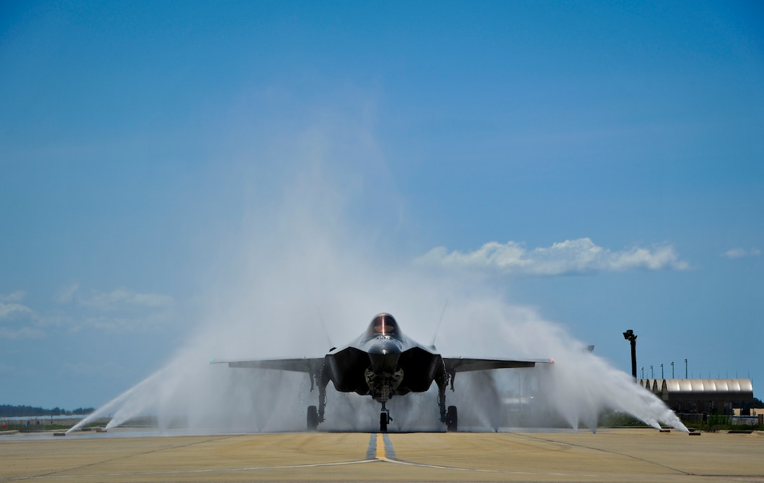 """Lt. Col. Christine Mau, 33rd Operations Group deputy commander, navigates her F-35A through the """"bird bath"""" after returning from her first flight on Eglin Air Force Base, Florida, May 5, 2015. Mau, who previously flew F-15E Strike Eagles, made history as the first female F-35 pilot in the program. (U.S. Air Force photo/Staff Sgt. Marleah Robertson)"""